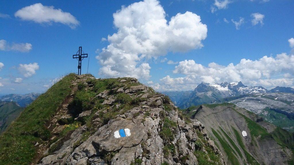 Gipfelkreuz Druesberg, SZ. Über dem Höch Hund leuchtet der Glärnisch. 16.7.2018